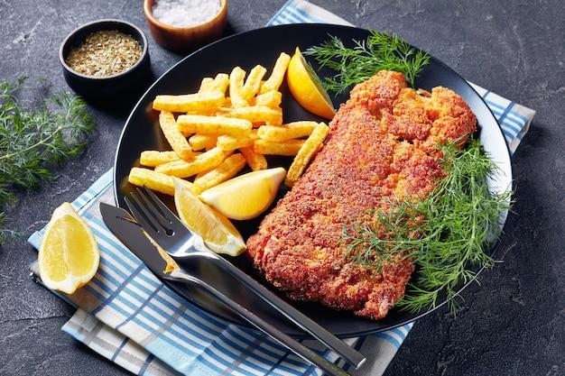 Close-up de filé de pescada à milanesa servido com batatas fritas, endro fresco e rodelas de limão em um prato preto sobre uma mesa de concreto, vista horizontal de cima