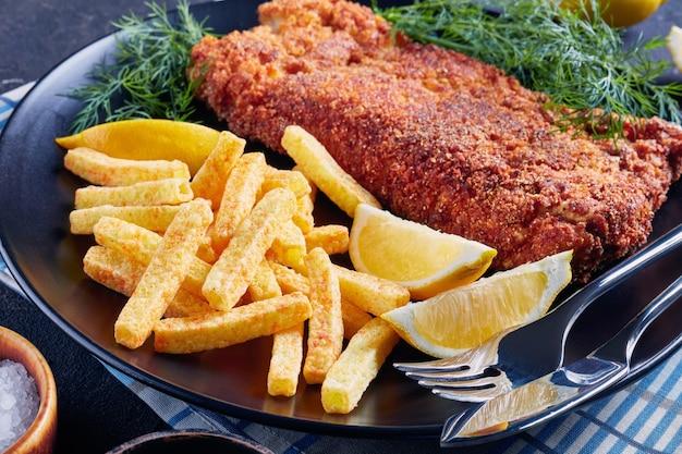 Close-up de filé de pescada à milanesa servido com batatas fritas, endro fresco e rodelas de limão em um prato preto sobre uma mesa de concreto