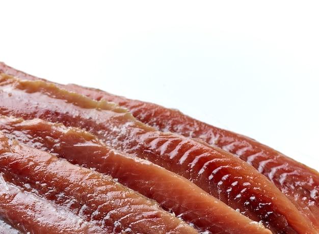 Close up de filés de anchova em lata em fundo branco