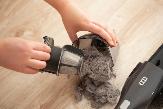 Close-up de filtro suja e fortemente obstruído do aspirador de pó manual, poeira e pó no filtro de vácuo doméstico