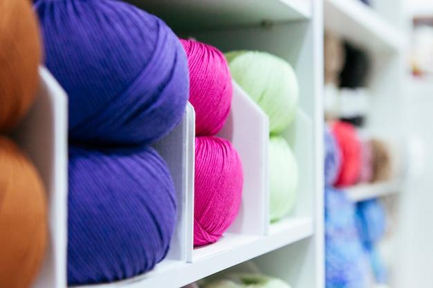 Close-up de fios de lã de armazenamento organizados por cores em uma prateleira