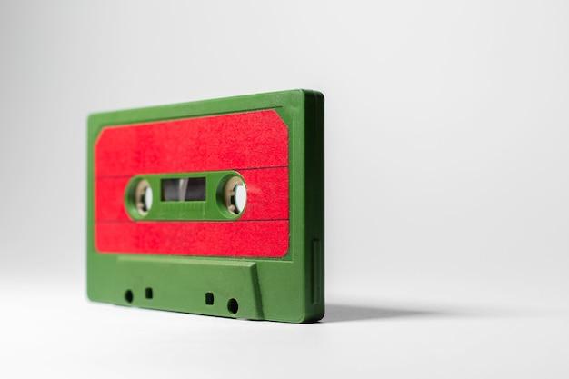 Close-up de fita cassete de música vintage verde-vermelho em branco.