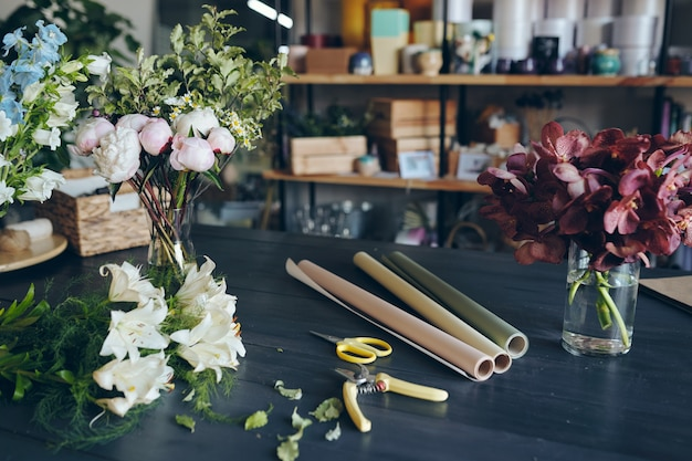 Close-up de flores em vasos, tesouras de podar, tesouras e papéis de embrulho enrolados usados para embalar buquê