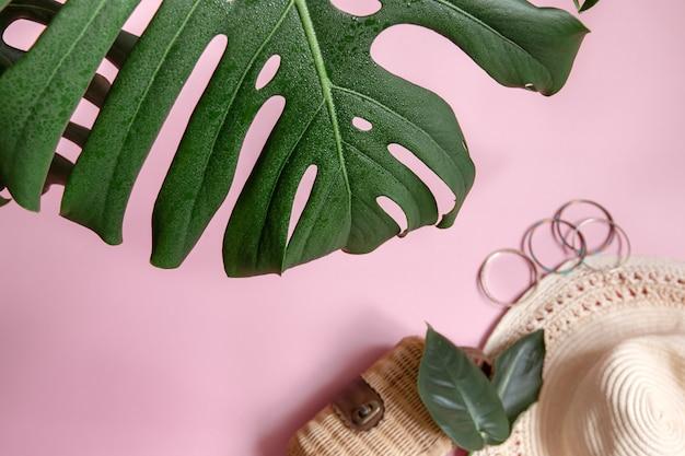 Close-up de folha natural e acessórios femininos em um fundo rosa, vista superior.