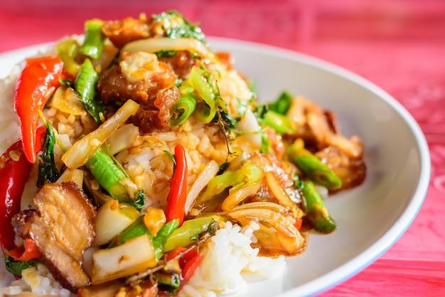 Close-up de folhas de manjericão fritas com carne de porco crocante no arroz, comida local tailandesa