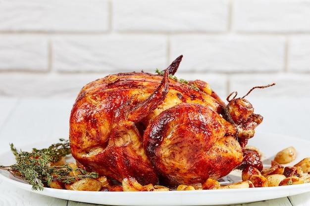 Close-up de frango assado com quarenta dentes de alho e frango com 40 dentes em uma travessa branca, em uma mesa de madeira com uma parede de tijolos brancos