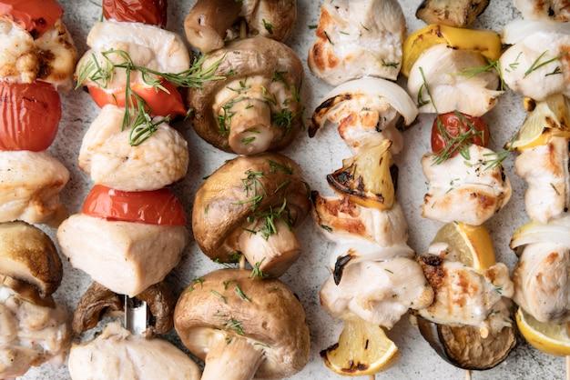 Close-up de frango grelhado e espetos de legumes