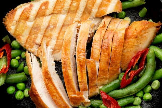 Close-up de frango grelhado em fatias e ervilhas com pimenta malagueta