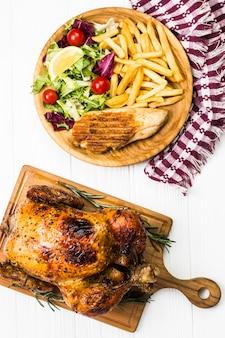 Close-up de frango perto de batatas fritas e salada