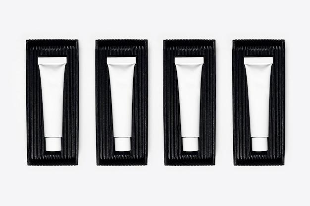 Close-up de frascos de tubo de cosméticos vazios, embalagem em caixa preta na superfície branca