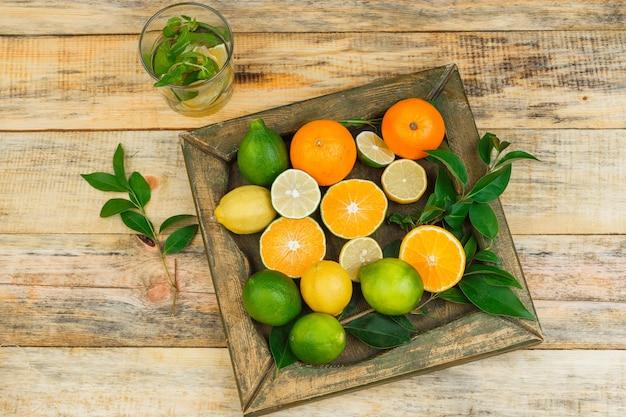 Close-up de frutas cítricas em prato de bronze com bebida fermentada