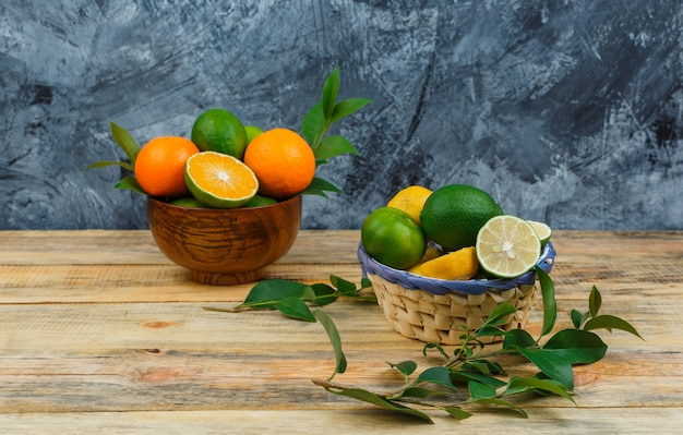 Close-up de frutas cítricas em tigelas com folhas na placa de madeira