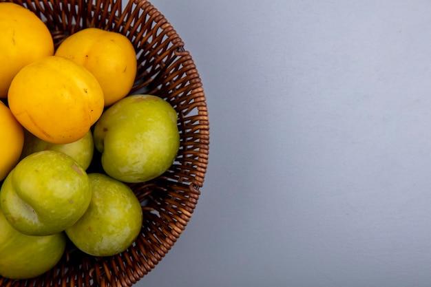 Close-up de frutas como pluots verdes e nectacots em uma cesta em um fundo cinza com espaço de cópia