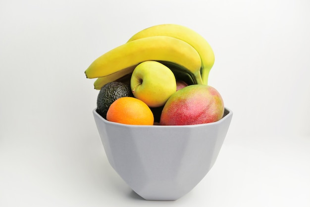 Close up de frutas doces em um vaso moderno em fundo branco.