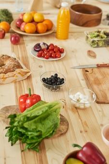 Close-up de frutas e vegetais frescos na mesa da cozinha de madeira