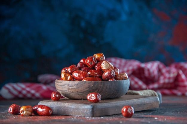 Close-up de frutas frescas de amora silvestre crua em uma tigela sobre uma tábua de madeira em misturar cores de fundo