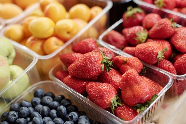 Close-up de frutas frescas e bagas em recipientes de plástico colocados no balcão de um mercado de alimentos
