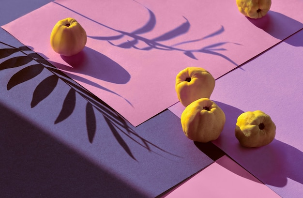 Close-up de frutas maduras de marmelo japonês doce em papel em camadas geométricas rosa e roxo.