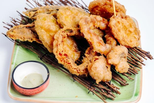 Close-up de frutos do mar fritos crocantes, servido no tabuleiro de pau no fundo branco