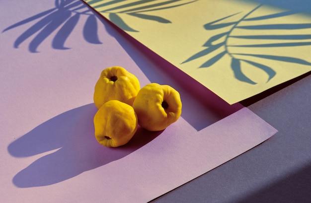 Close-up de frutos maduros de marmelo japonês doce em papel em camadas geométricas rosa e amarelo.
