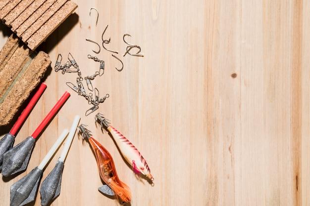 Close-up de gancho de pesca; isca de pesca; cortiça com linha de pesca e chumbadas no pano de fundo de madeira