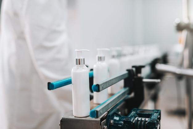 Close-up de garrafas com condicionador de cabelo em linha na saída da máquina de vazar