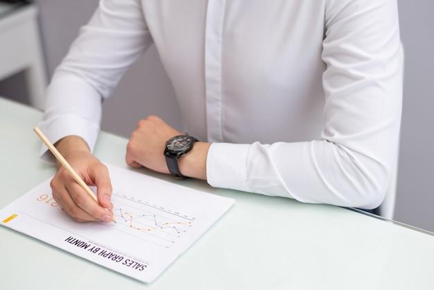 Close-up, de, gerente, sentando tabela, e, leitura, relatório vendas