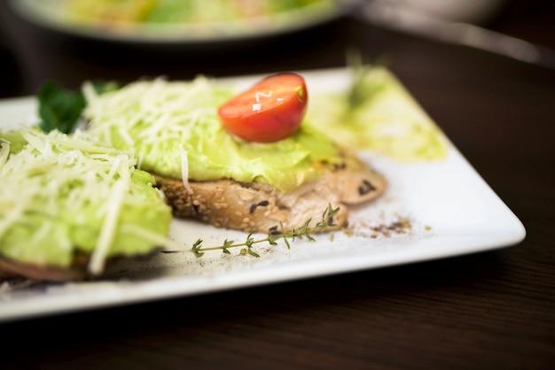 Close-up, de, gostosa, pão, com, pesto, molho, e, tomate cereja, ligado, prato