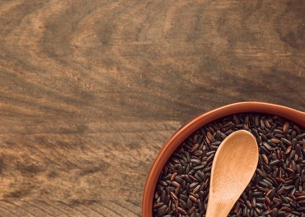 Close-up de grãos de arroz integral em taças na mesa de madeira