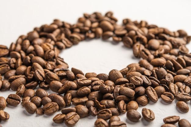 Close up de grãos de café espalhados em uma superfície clara centrada para foco seletivo de texto