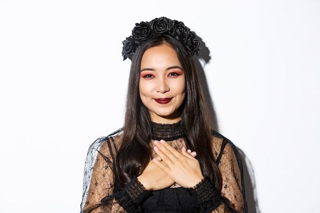 Close-up de grata sorridente mulher asiática parecendo grata com as mãos no peito, em pé com a fantasia de bruxa sobre fundo branco.