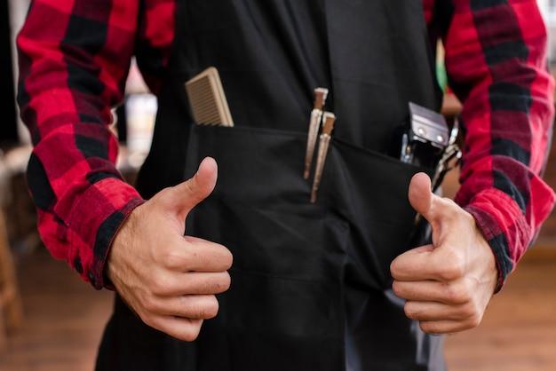 Close-up de haidresser mostrando os polegares