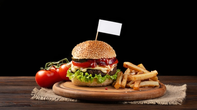 Close-up de hambúrguer caseiro com carne, tomate, alface, queijo e batatas fritas na tábua. pequena bandeira branca inserida no hambúrguer