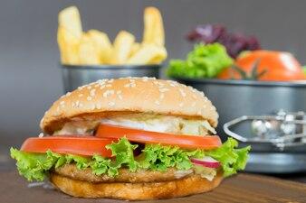Close-up de hambúrguer caseiro com legumes frescos e batatas fritas