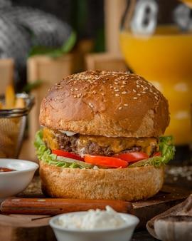 Close-up de hambúrguer de carne com queijo cheddar derretido, tomate, alface e maionese