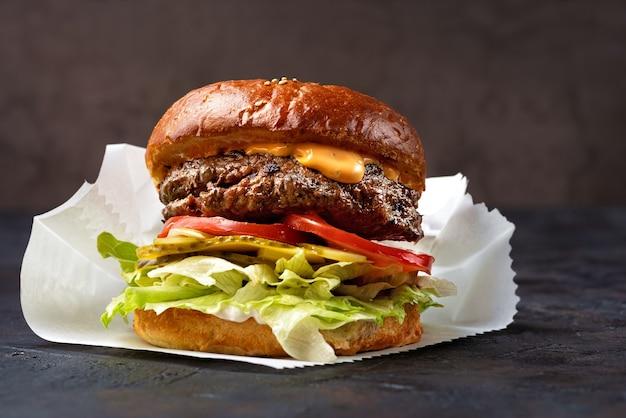 Close up de hambúrguer empilhado com coberturas frescas em pão artesanal de grãos inteiros, em uma superfície de pedra escura com fundo escuro e espaço de cópia