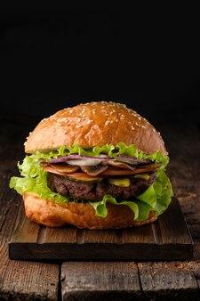 Close-up de hambúrguer saboroso feito em casa na mesa de madeira.