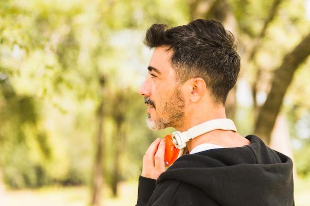 Close-up, de, homem, com, seu, headphone, ao redor pescoço, olhando