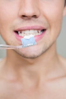 Close-up, de, homem, dentes escovando, em, banheiro