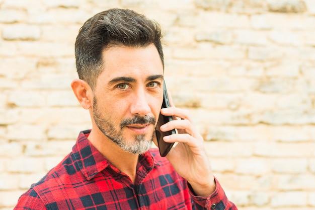 Close-up, de, homem, em, camisa xadrez vermelha, falando telefone móvel, olhando câmera