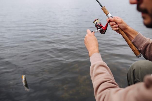 Close-up, de, homem, girar, bobina, para, apanhar, a, peixe, de, água
