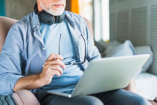Close-up, de, homem idoso, segurando, espetáculos, usando computador portátil