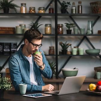 Close-up, de, homem jovem, comer, maçã verde, olhar, tablete digital