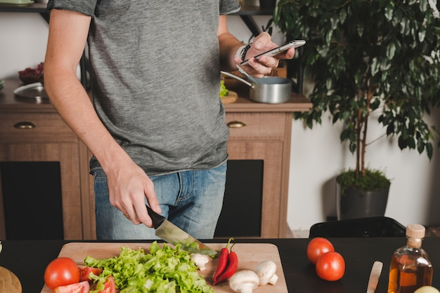 Close-up, de, homem, legumes cortantes, com, faca, usando, cellphone