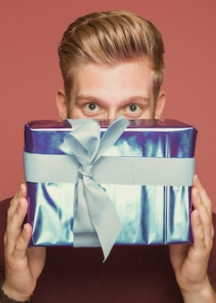 Close-up, de, homem, segurando, embrulhado, caixa presente, sob, seu, olhos