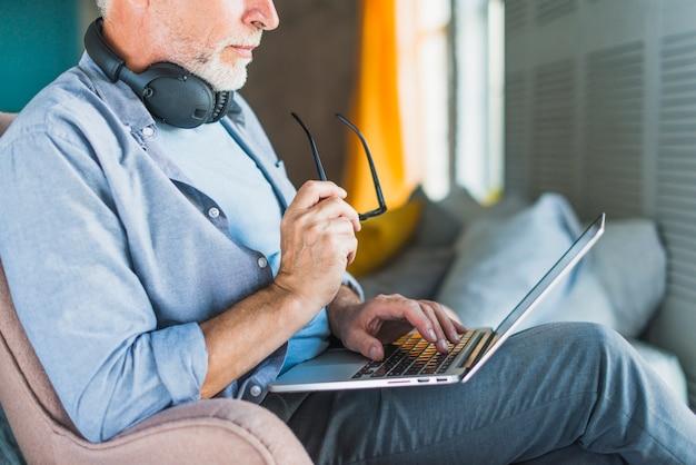 Close-up, de, homem, segurando óculos, usando computador portátil