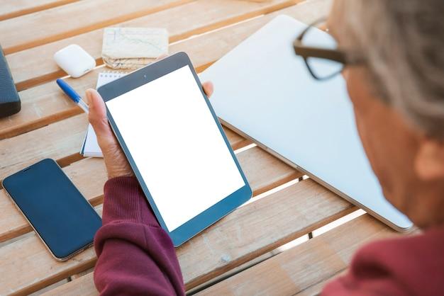 Close-up, de, homem sênior, olhar, tablete digital, com, em branco, tela branca, ligado, tabela madeira