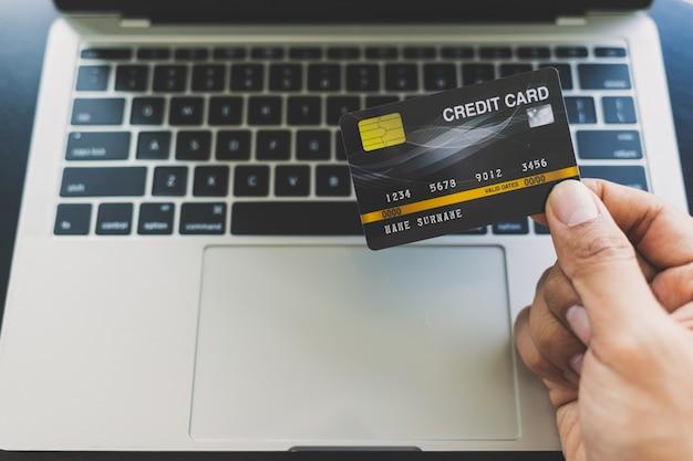 Close-up de homens asiáticos, segurando um cartão de crédito e fazer compras on-line via laptop