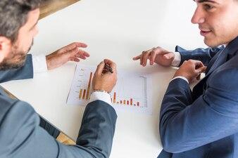 Close-up, de, homens negócios, trabalhando, companhia, relatório financeiro, sobre, a, branca, escrivaninha