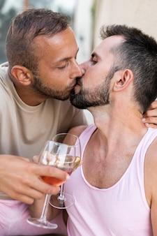 Close-up de homens se beijando e brindando